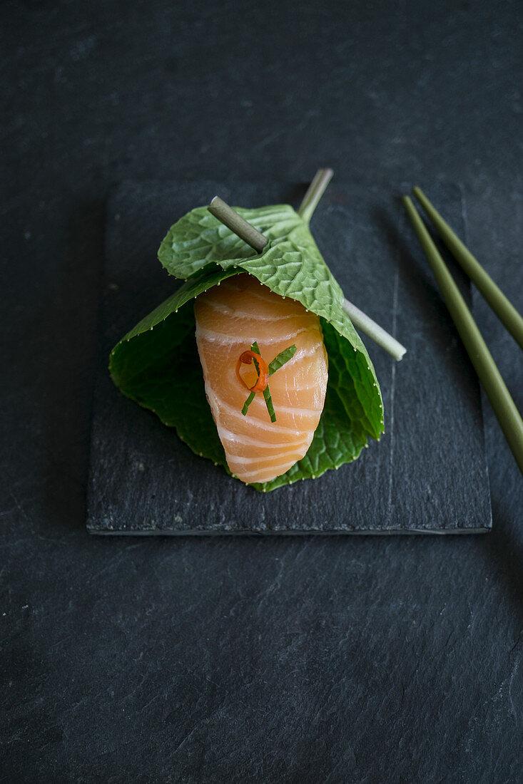 Nigiri sushi with salmon in a fresh wasabi leaf