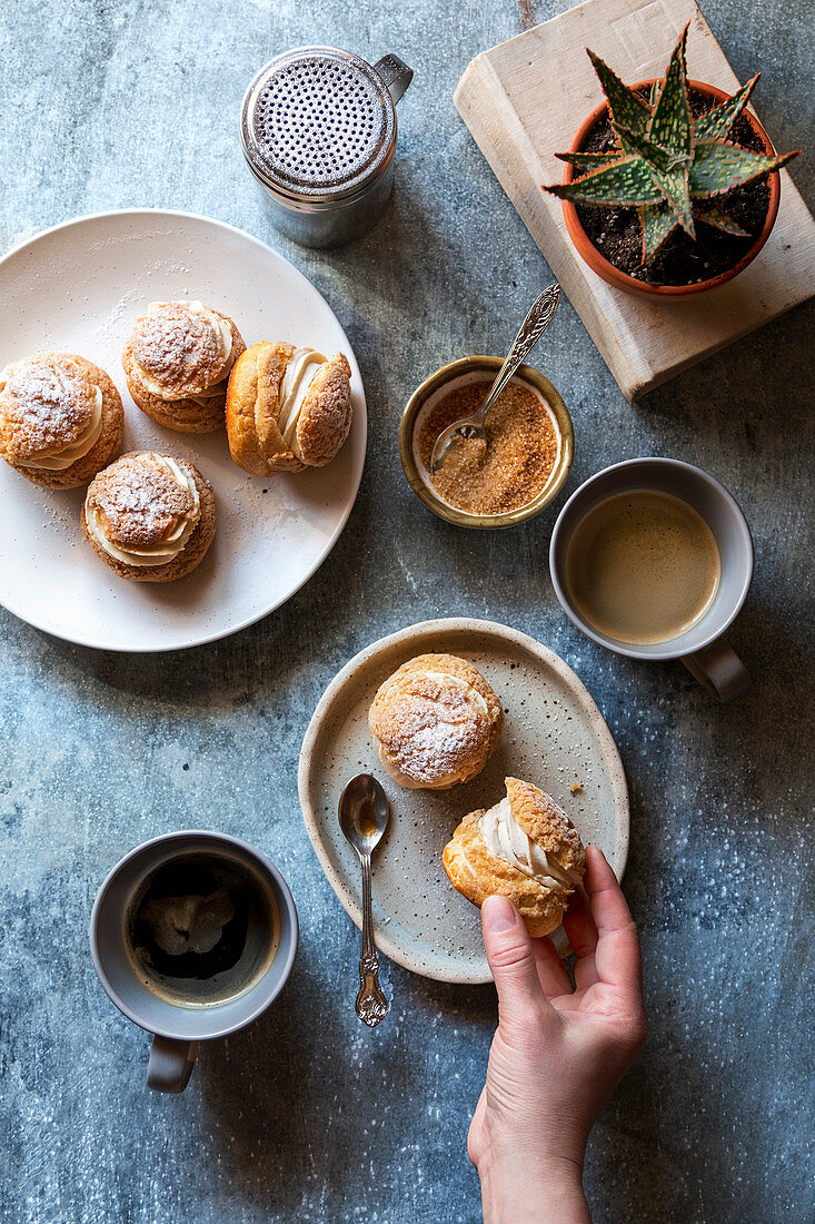 Female hand grabbing a choux au craquelin from the plate