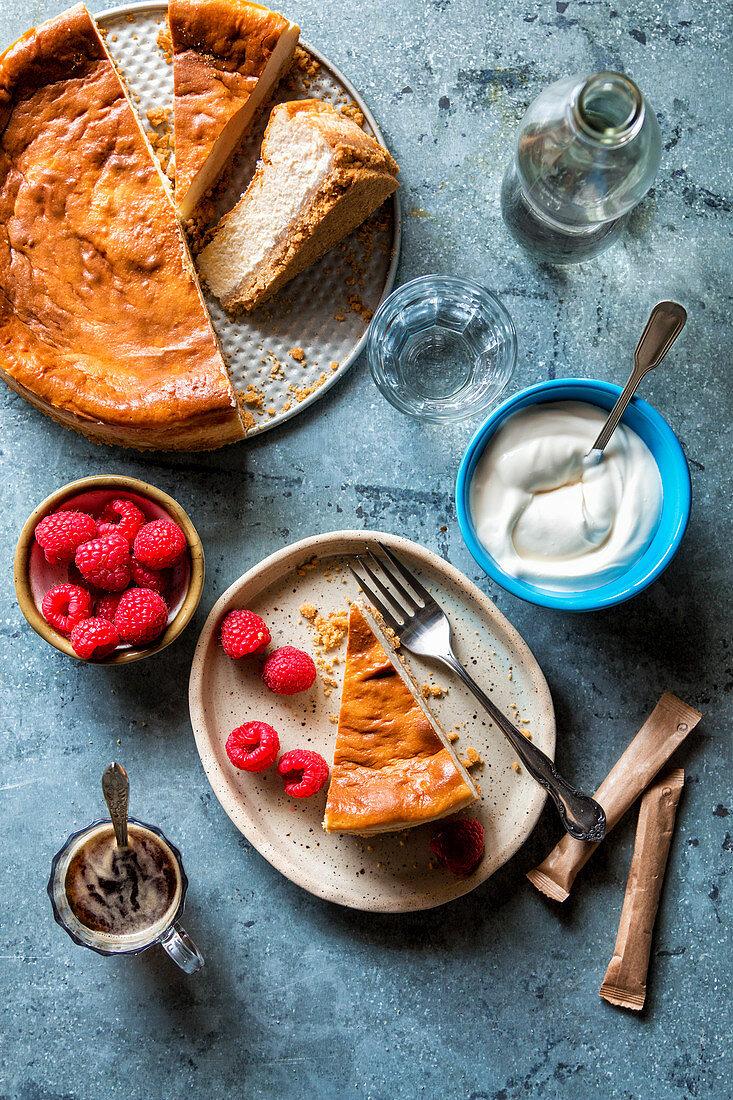 Sliced cheesecake served with raspberries and crème fraiche