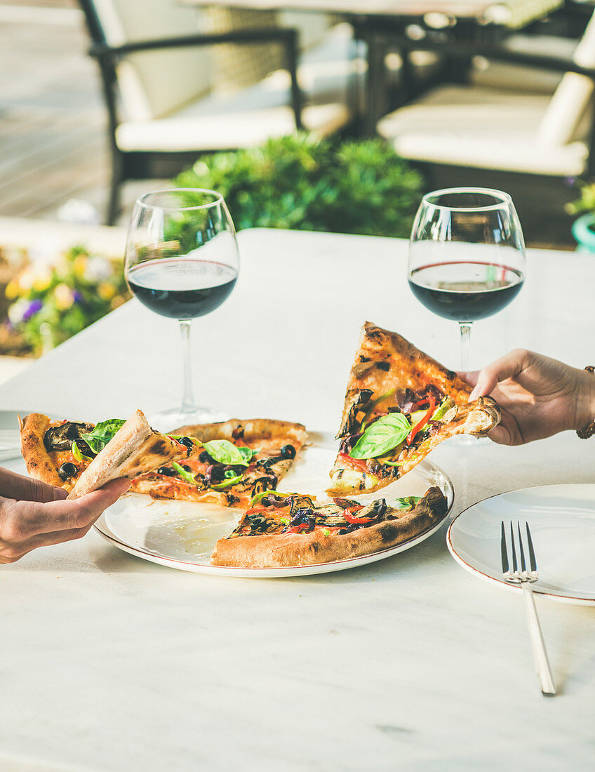 People eating freshly baked Italian vegetarian pizza with vegetables and fresh basil and drinking red wine in outdoor restaurant