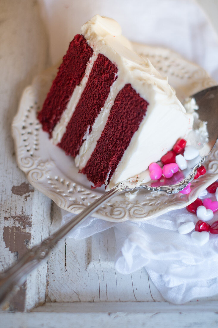 A piece of red velvet cake and heart drops