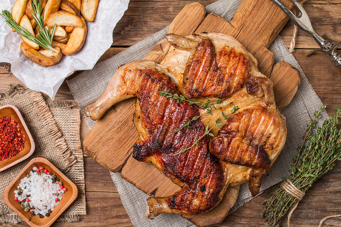 Grilled fried roast Chicken tobacco on cutting board with potato on wooden background