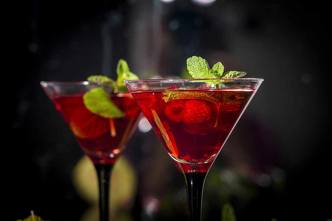 Two martini glasses of red alcohol raspberry cocktail with mint