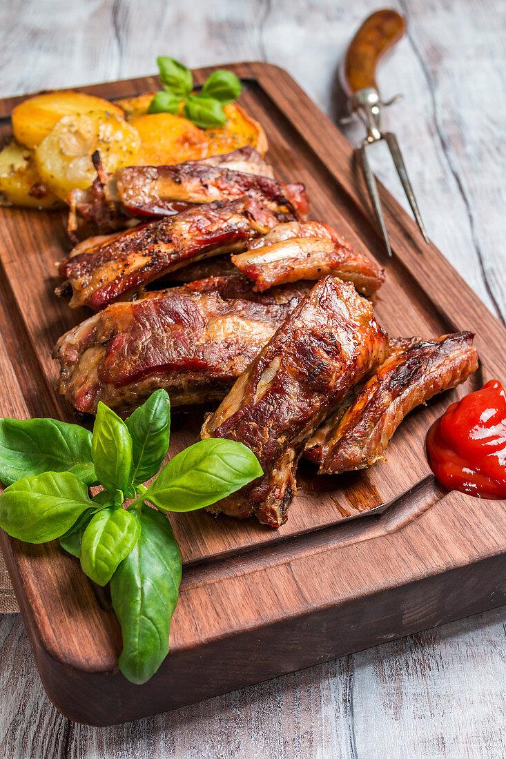 Gegrillte Schweinerippen mit Bratkartoffeln, Ketchup und Basilikum