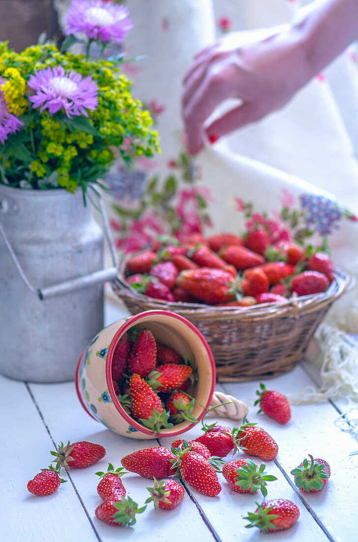 Strawberries in a basket and an upset cup