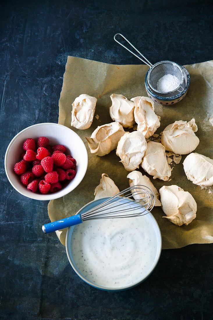 Selbstgemachtes Meringue serviert mit Himbeeren und Joghurtcreme