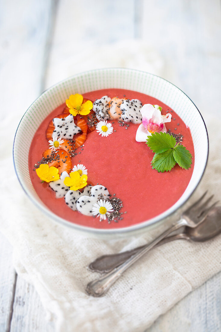 A strawberry smoothie bowl with banana, oats, dragon fruit and edible flowers (vegan)