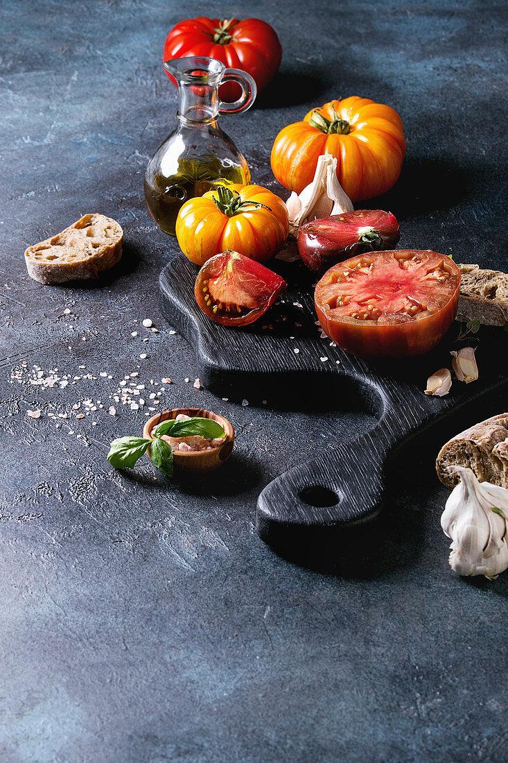 Gelbe und rote Bio-Tomaten mit Zutaten für Bruschetta auf Holzbrett