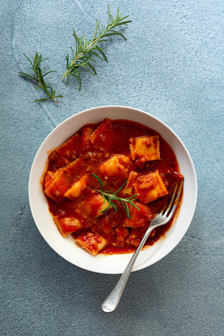 A bowl of ravioli in tomato and meat sauce with a fork on a blue textured background