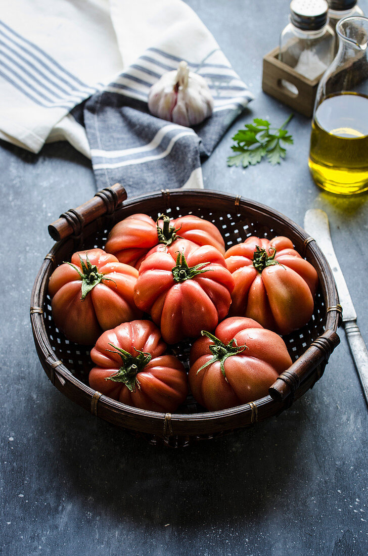 Freshly picked beef tomatoes in a wicker basket against a dark background