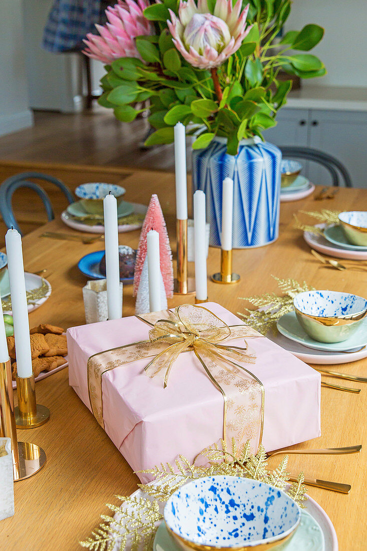 Pink gift, candles and flowers on the laid table