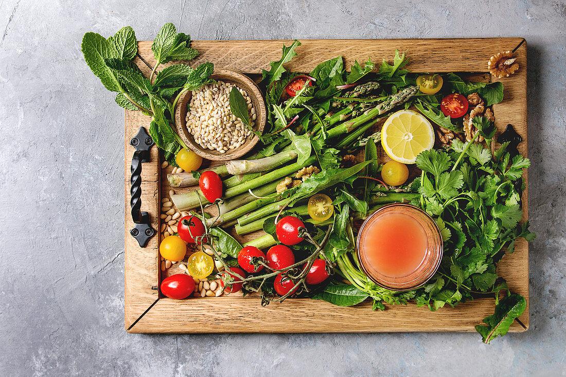 Variety of vegetarian healthy eating food ingredients. Green asparagus, herbs, tomatoes, nuts, wheat corns, dandelion leaves, glass of juice