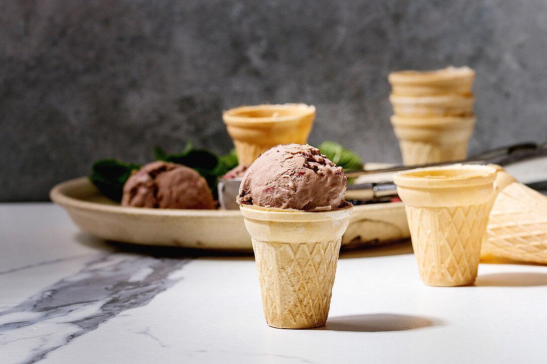 Homemade chocolate raspberry ice cream in small waffle cup