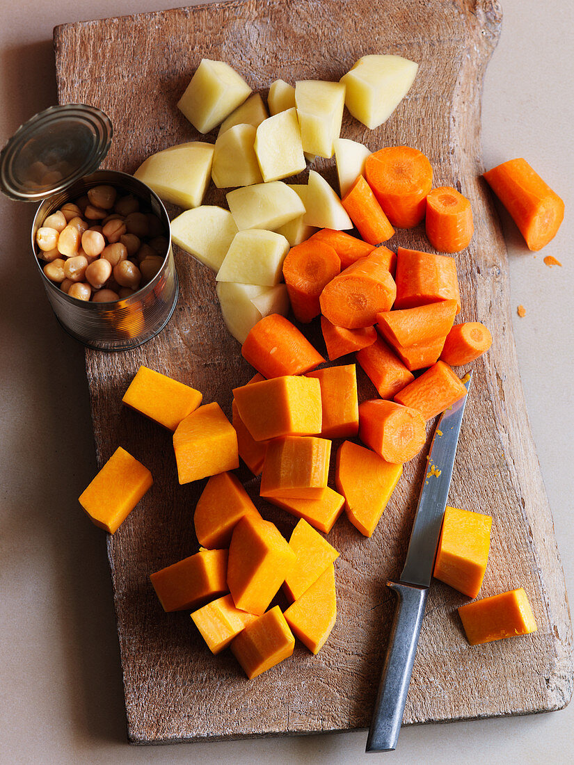 Sliced vegetables (carrots, sweet potatoes, potatoes) and jar of chickpeas