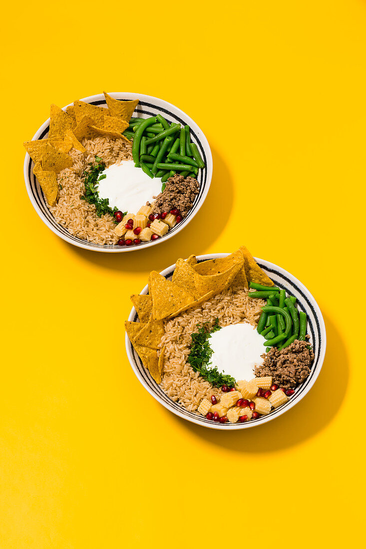 Tex Mex bowl with wholemeal rice, taco chips and pomegranate seeds