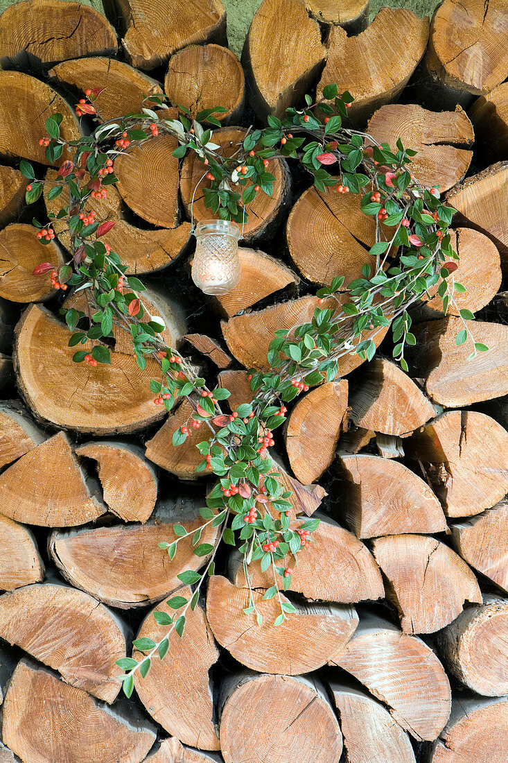 Heart-shaped wreath of cotoneaster around candle lantern on stacked firewood