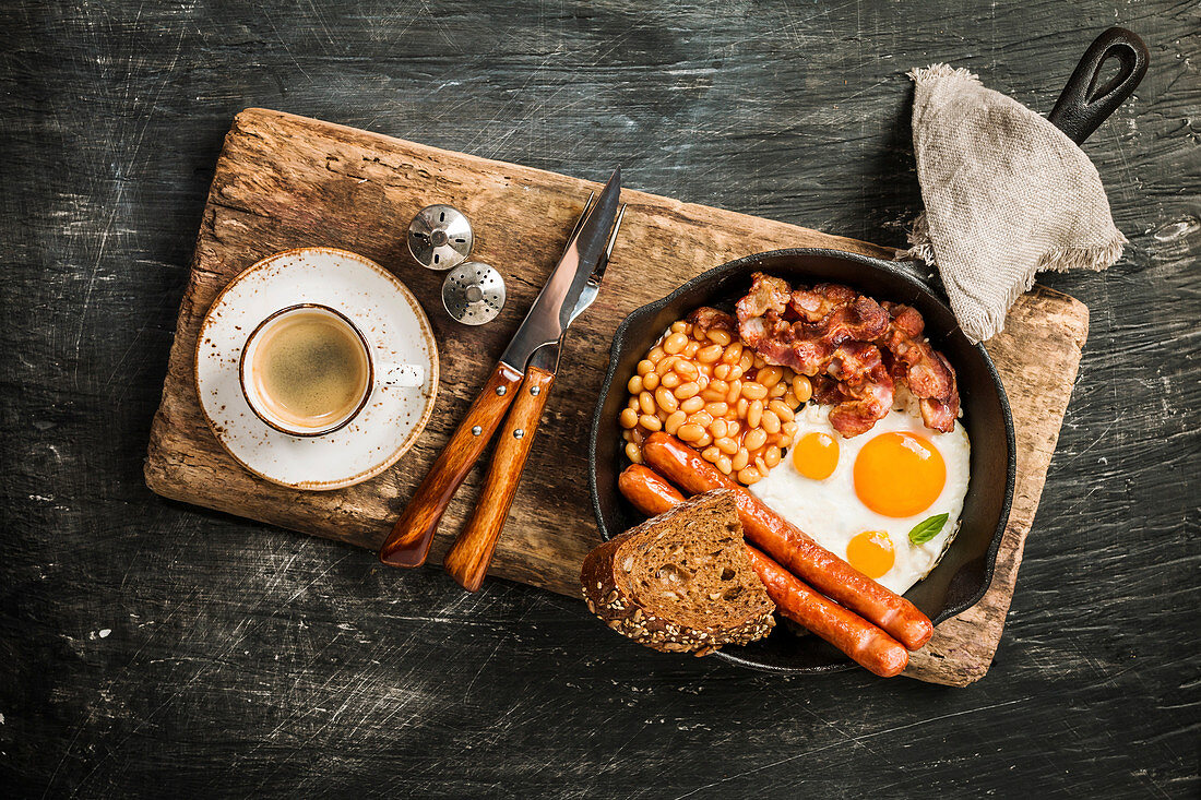 English breakfast - fried egg, beans, tomatoes, sausages, bacon and bread in frying pan