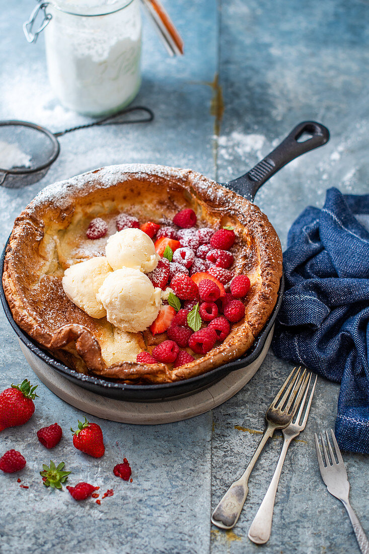 Baby dutch pancake in a skillet with fresh berries and ice cream