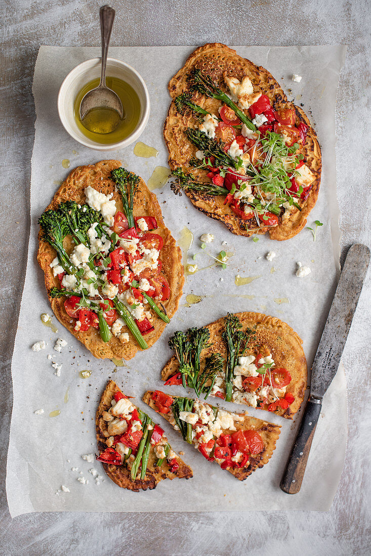 Socca (chickpea flour pancake) pizza with peppers, tomatoes, broccoli and feta cheese