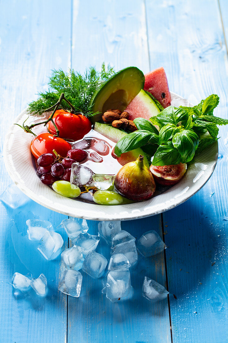 Tomatoes, fruits and basil on a plate with ice cubes