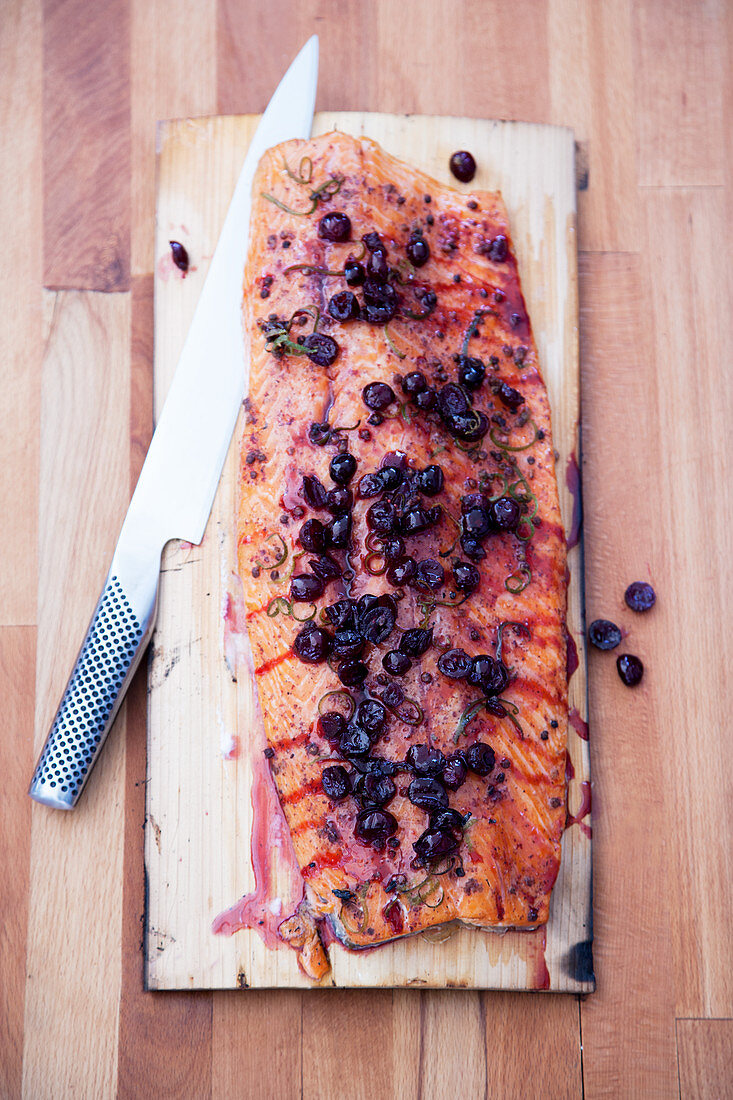 Dry marinated salmon on a plank with cranberry sauce