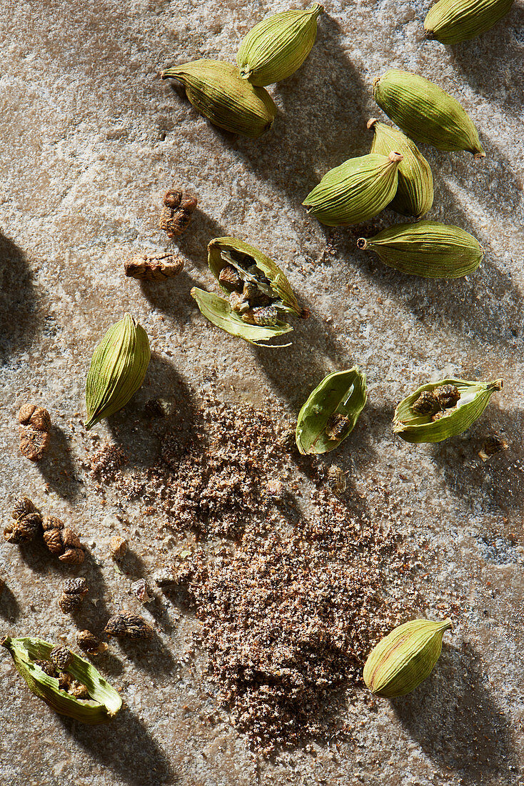 Cardamom pods with ground cardamom on stone from overhead
