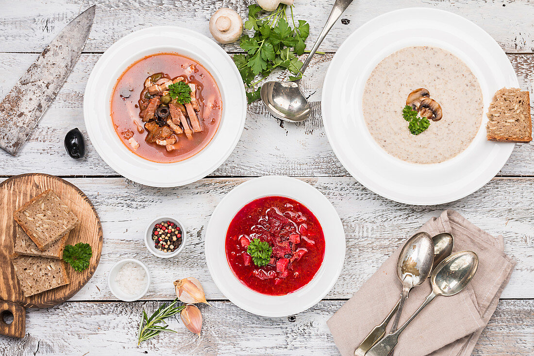 Three soup varieties: soljanka, mushroom cream soup, and beetroot soup