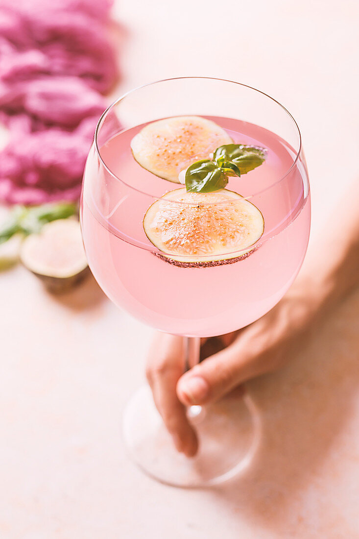 Woman holding pink cocktail with fig and basil