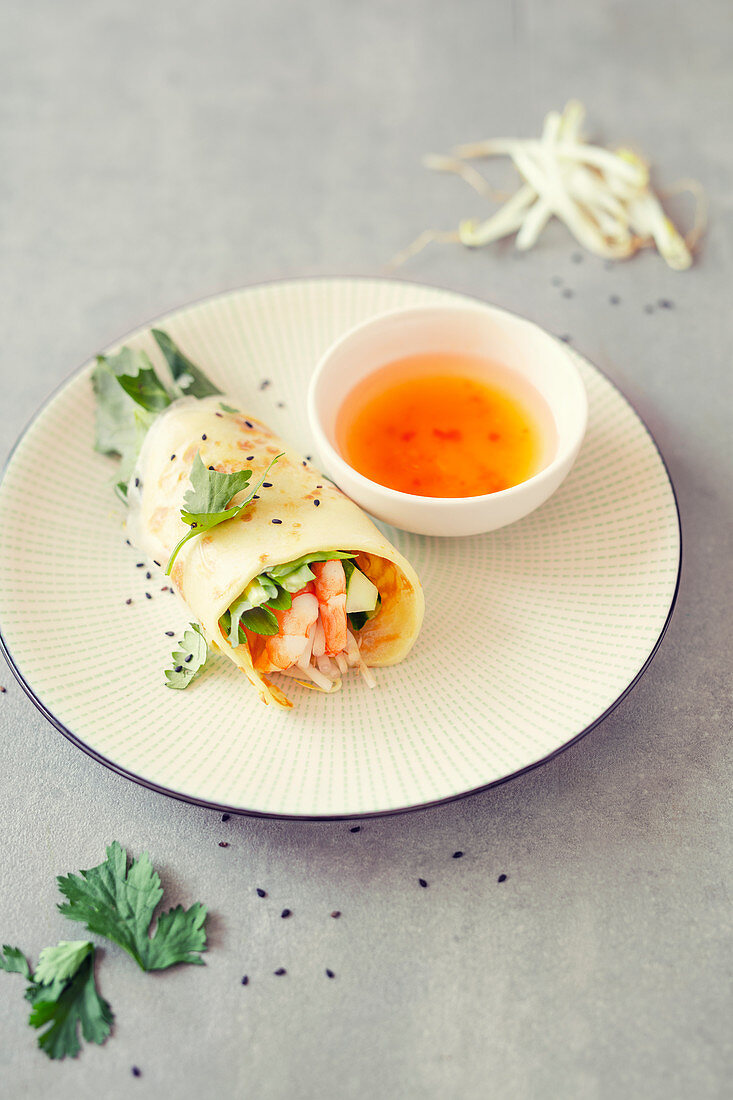 Stuffed coconut pancakes with shrimps and salad in rice leaf (Vietnam)