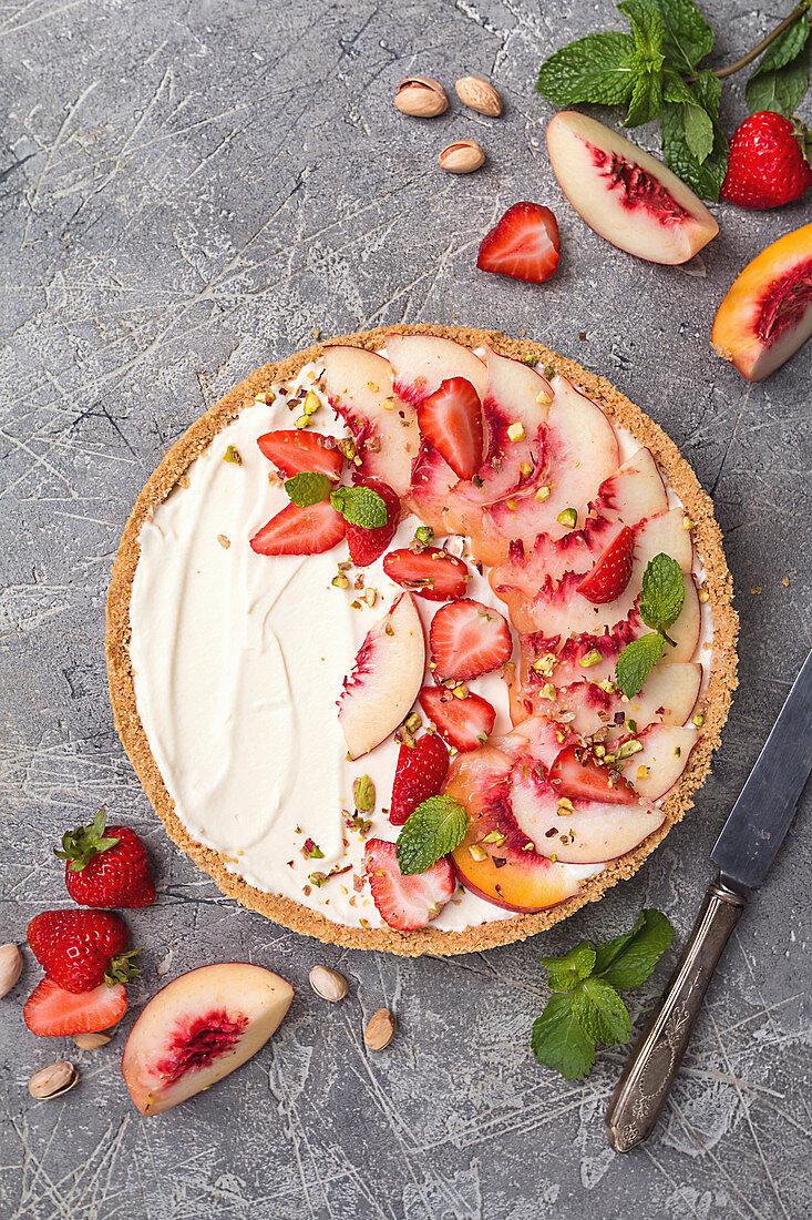 Tart with honey and mascarpone cheese cream, fresh peaches and strawberries