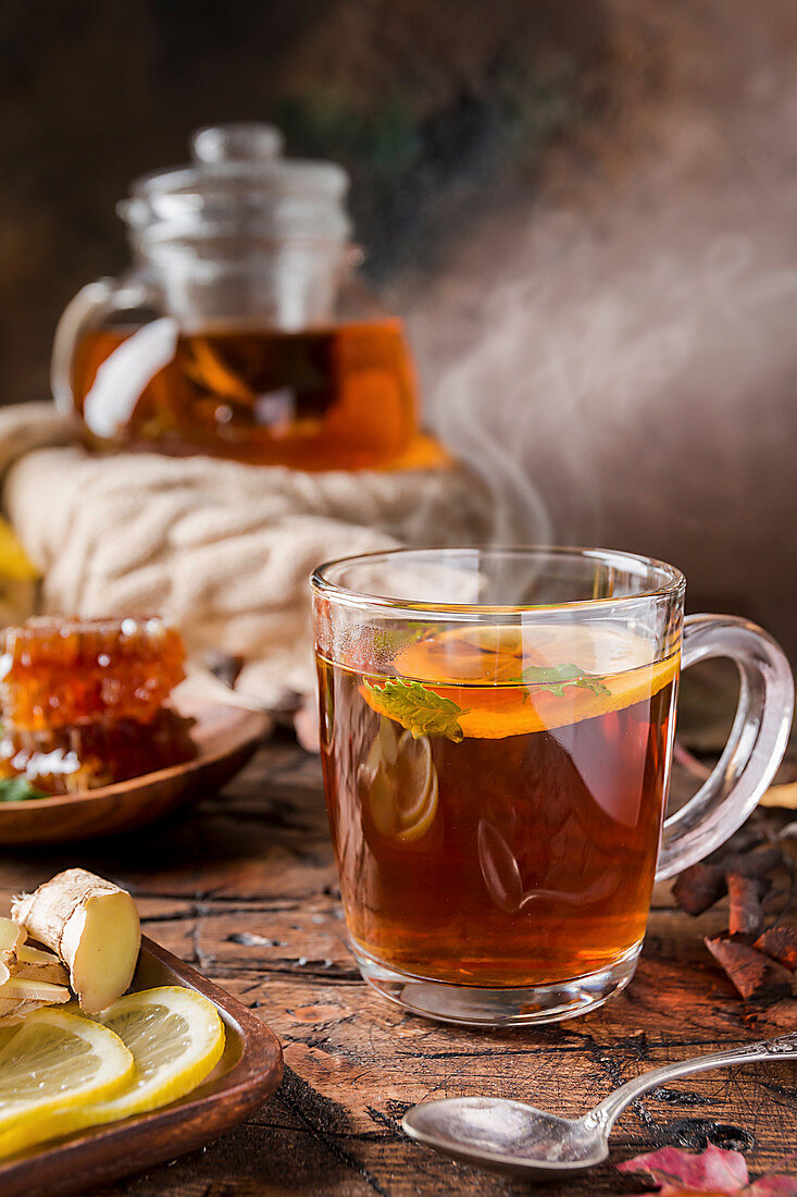 Glass cup of hot tea with mint, honey, ginger and lemon