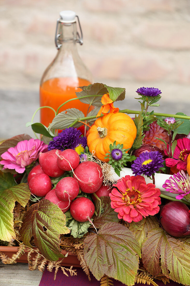 Colourful autumn arrangement of flowers and vegetables for harvest festival