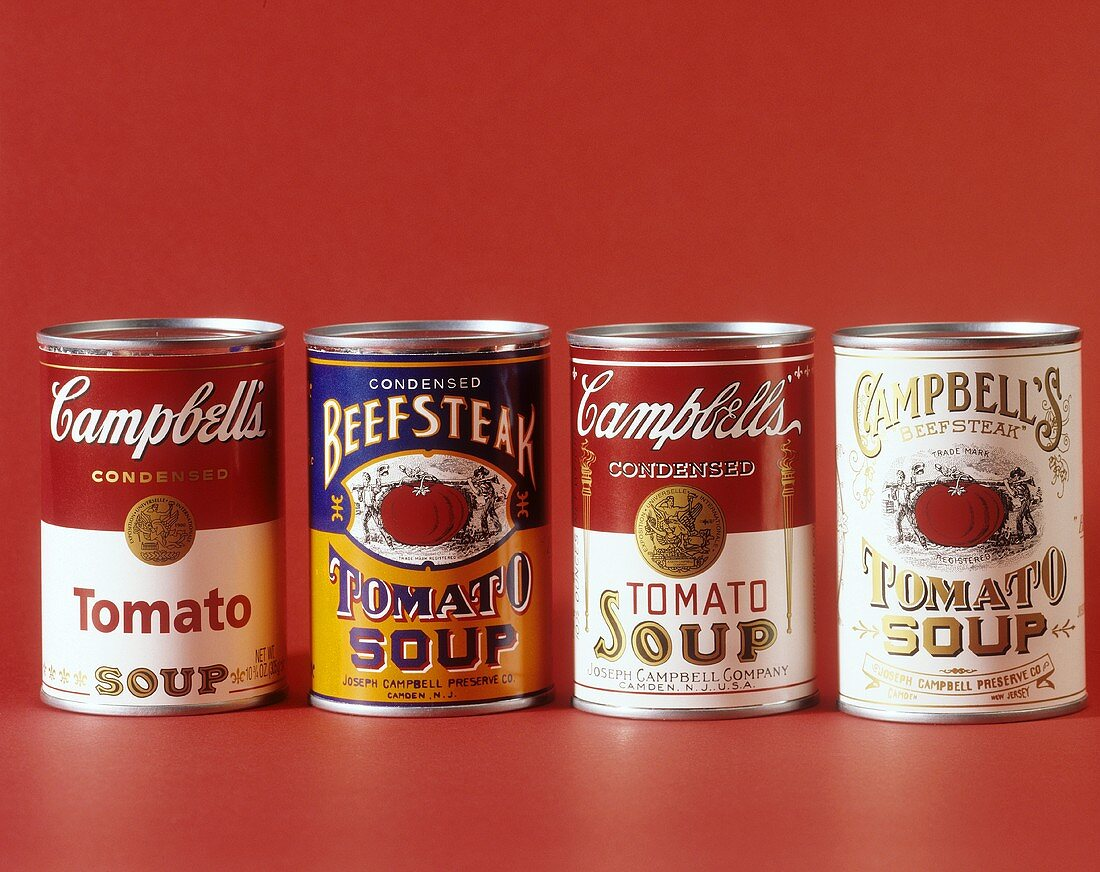 Four tins of Campbell's Tomato Soup against red background