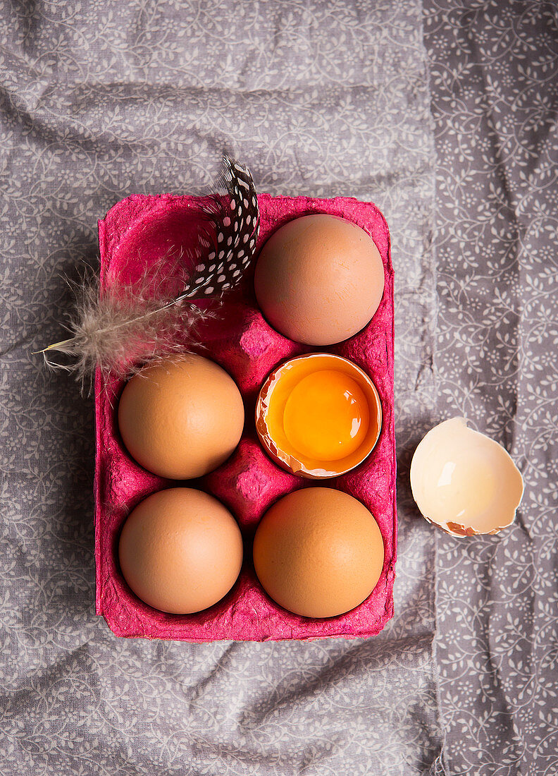 Pink Box of five fresh eggs one cracked open and in shell showing yolk and a feather on the box