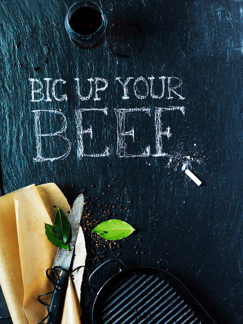 A blackboard wtih 'Big Up Your Beef' written in chalk, a knife, bay leaf, a griddle, and black pepper