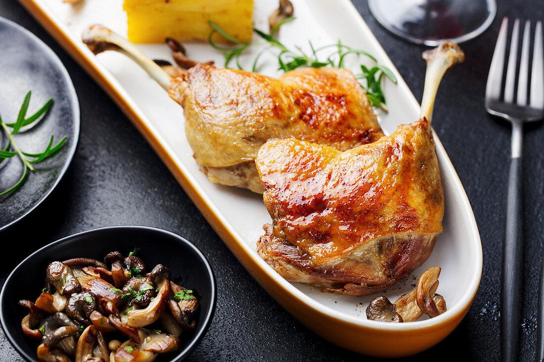 Duck legs confit with potato gratin and mushroom sauce