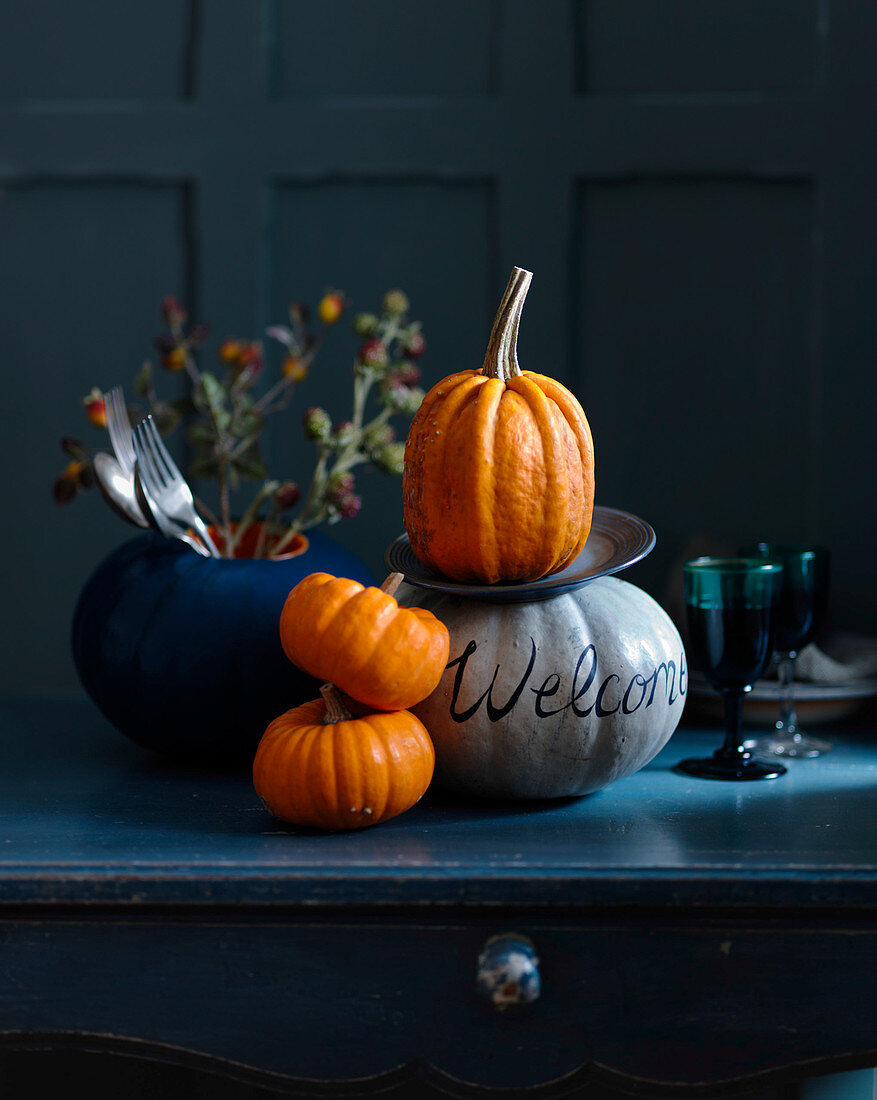 Decorative pumpkins with cutlery, flowers, and glasses of wines