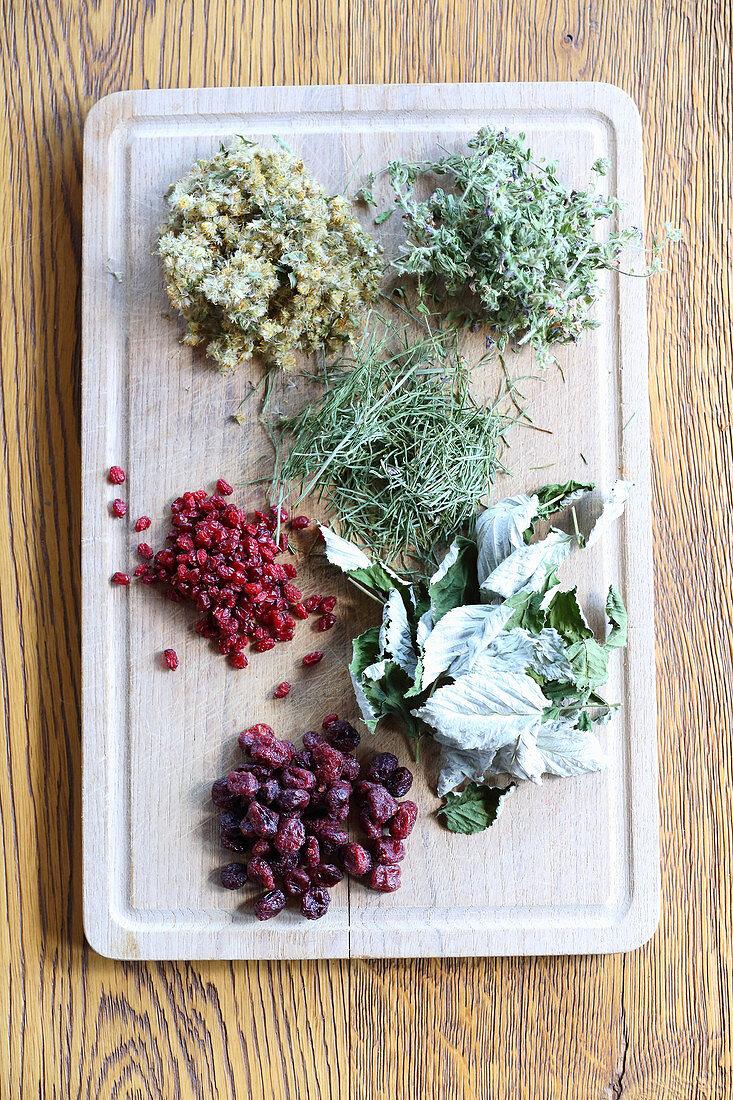 Getrocknete Blätter und Beeren für Tee auf einem Holzbrett