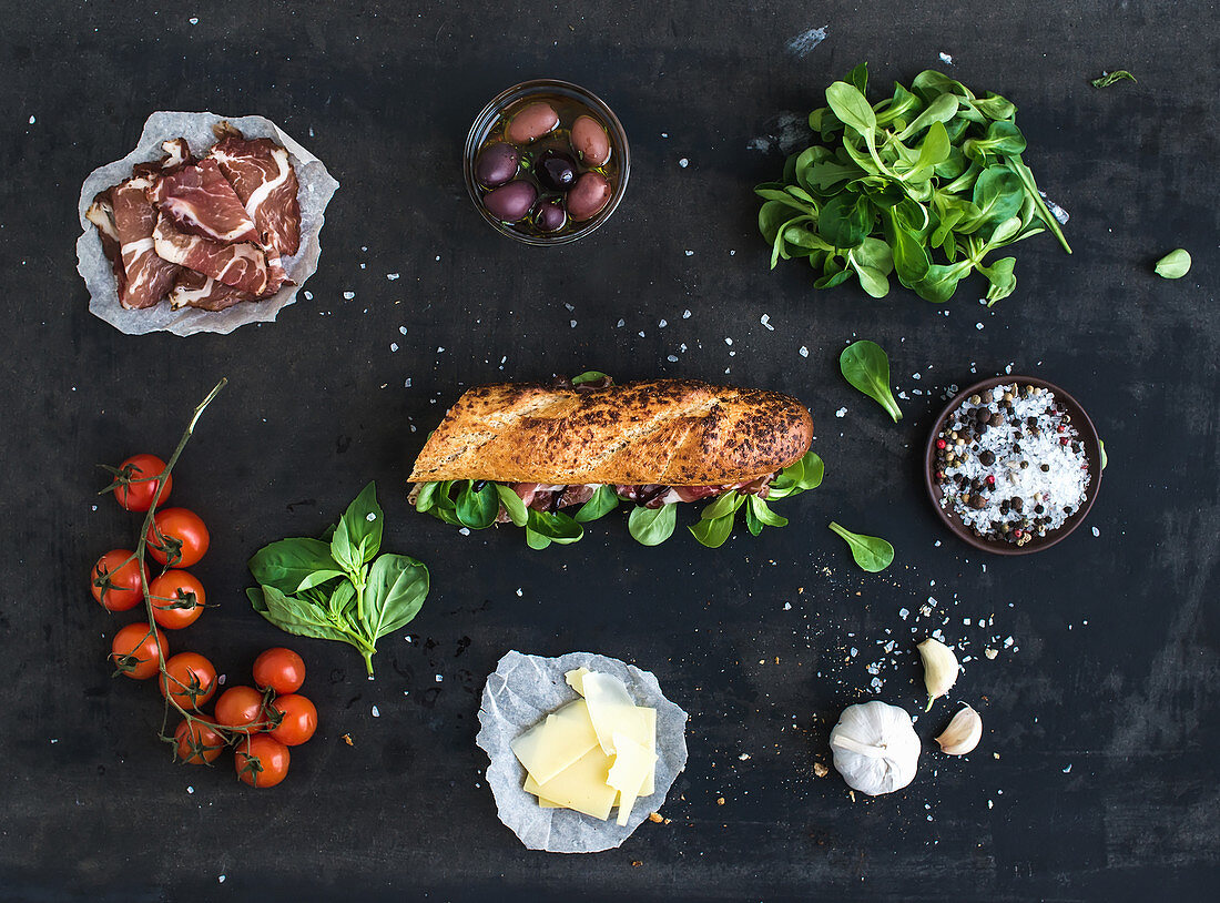 Ingredients for sandwich with smoked meat, basil, arugula, olives, cherry-tomatoes, parmesan cheese, garlic and spices