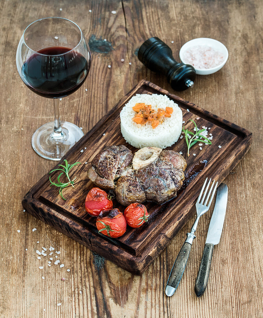 Roast beef Ossobuco with rice, vegetables and glass of wine