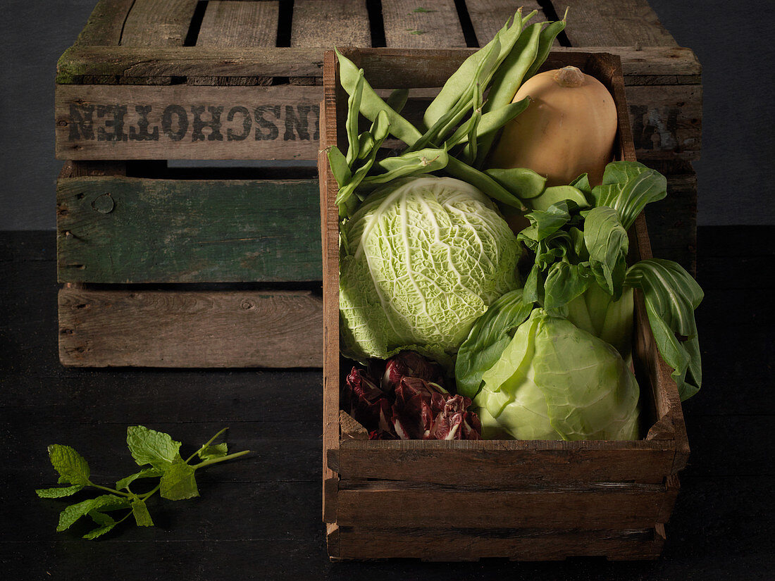 A vegetable crate with cabbages, squash and green beans