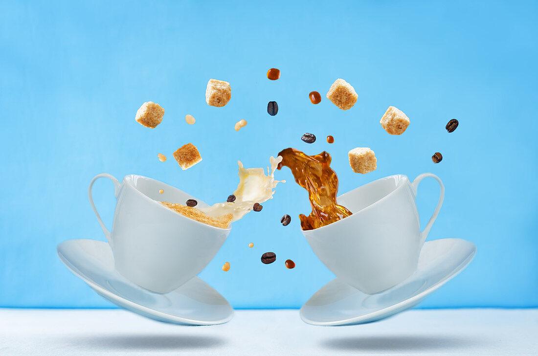 Fliegende Tassen mit Kaffee, Zucker und Kaffeebohnen vor blauem Hintergrund