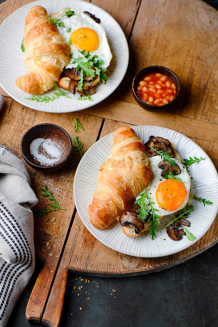 A croissant sandwich with fried eggs and mushrooms