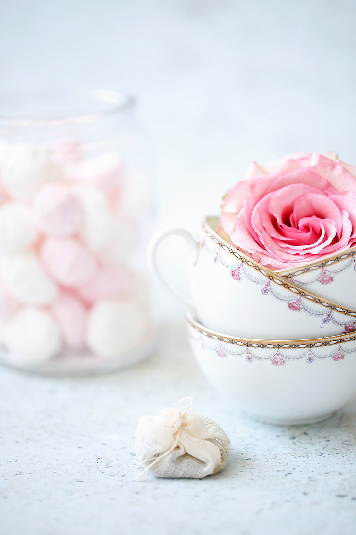 A still life with tea cups, rose petals, tea bags and meringues in a glass