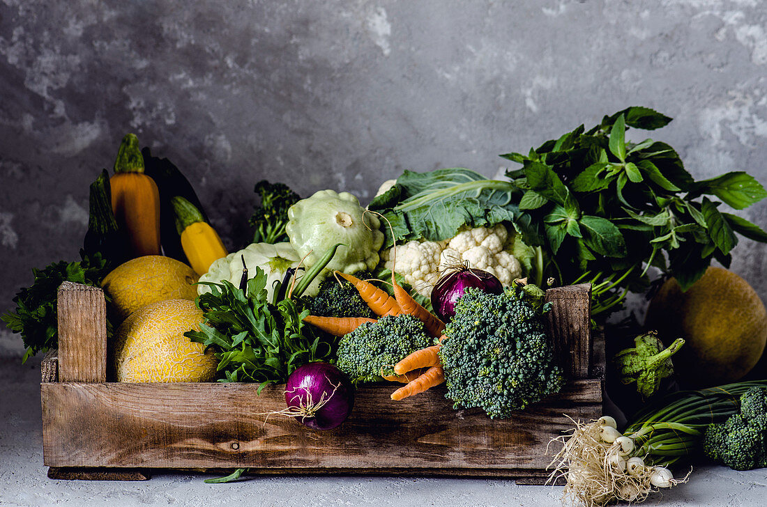 A vegetable box with cabbage, onions and pumpkin