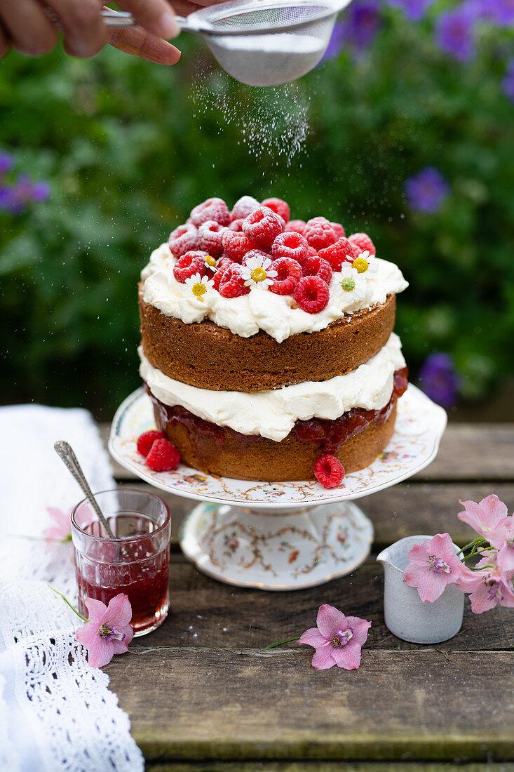 Victoria Sponge Cake mit Himbeeren, Sahne und Puderzucker auf Gartentisch