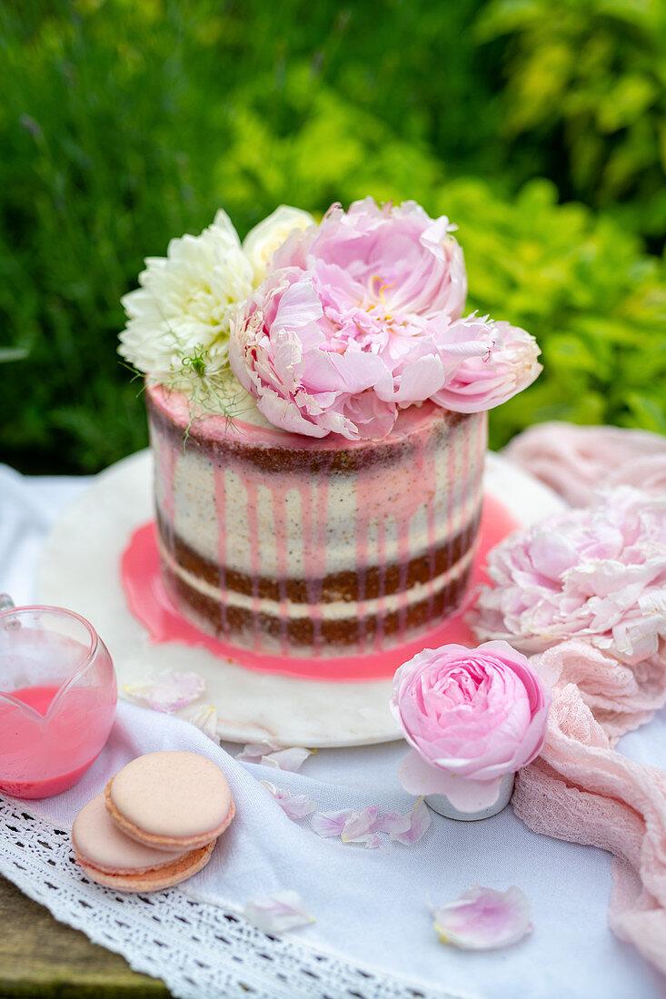 Romantische Torte mit frischen Pfingstrosen auf Gartentisch