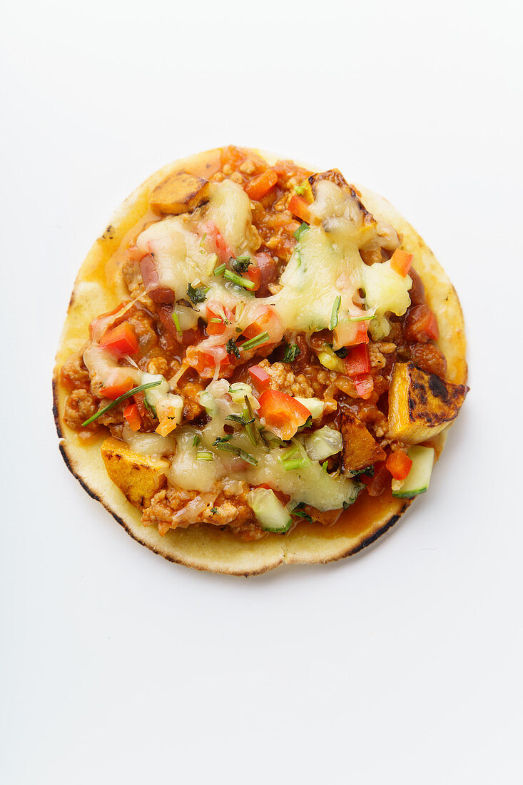 Mexican taco with chili con carne, grilled sweet potatoes and grated cheese on white background