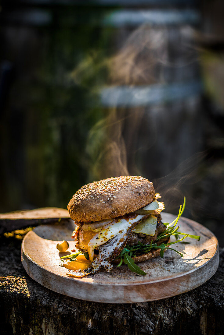Grilled burger with fried egg, rocket and cheese