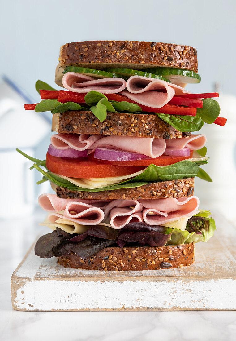 A triple-decker sandwich on a wooden board